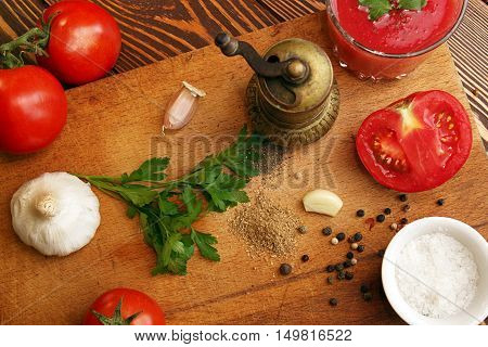 Tomato juice and spacies. Ingredient for cooking of tomato soup on chopping board