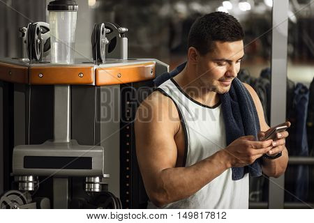 Always connected. Pleasant joyful positive man holding his cell phone and choosing a person to call while standing in a gym