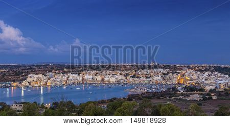 Marsaxlokk Malta - Panoramic skyline view of Marsaxlokk the traditional fisherman village of Malta at sunrise with blue sky and beautiful clouds