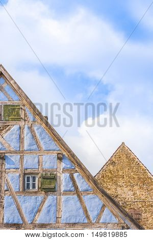 Details of medieval german gable roofs  - Medieval architecture background with two german gable roofs one house with blue half timbered walls and one with aged stone wall.