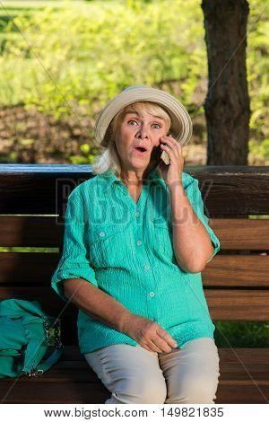 Surprised woman with a phone. Senior lady on the bench. Tariff with lowest prices. Cheap calls to any country.