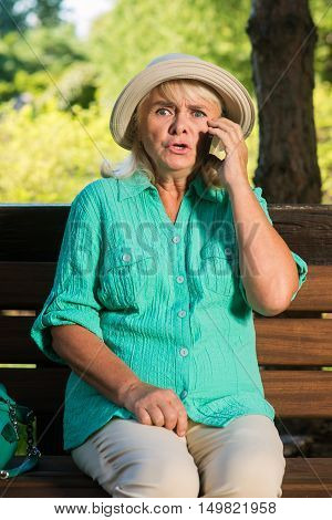 Scared woman with a phone. Senior lady on park bench. I hear terrible things. Problems came suddenly.