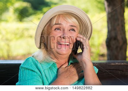 Smiling mature woman with phone. Happy lady wearing a hat. Congratulations from grandson. Priceless moments of life.