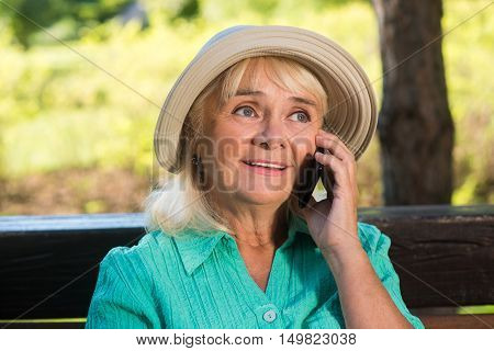 Senior woman on the phone. Mature lady in a hat. Stay in touch with relatives. Cheap calls abroad.