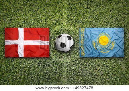 Denmark vs. Kazakhstan flags on green soccer field, 3D illustration