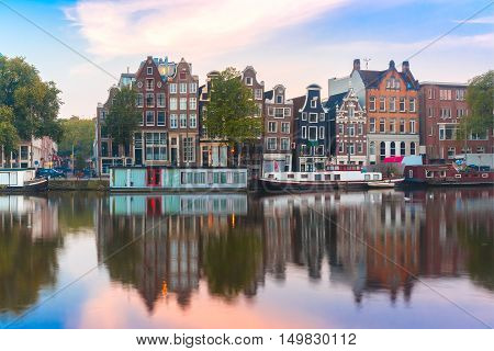 Amsterdam canal Amstel with typical dutch houses and boats during sunrise, Holland, Netherlands.