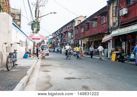 Shanghai China - October 18 2006: People go to the grocery store in a suburban street with typical houses and shops
