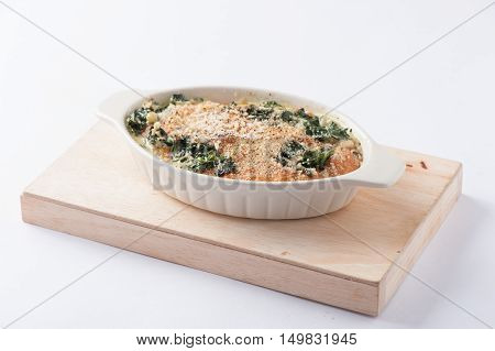 Modern style Spinach gratin (baked spinach with chesse) in ceramic bowl on wood plate isolated on white background with clipping path