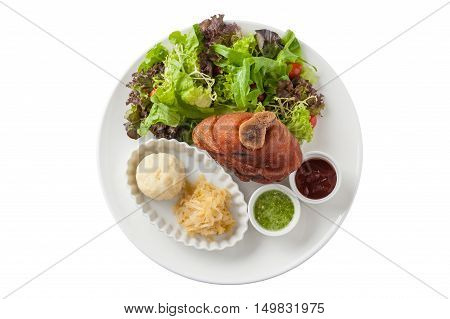 Top view of German Pork Hocks or pork knuckle with barbecue sauce Thai spicy sauce mashed potatoes pickled cauliflower and fresh vegetables in ceramic dish isolated on white backgrund