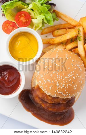 American style barbecue pork burger set including french fries ketchup mustard sauce garnished with fresh vegetables in caramic dish