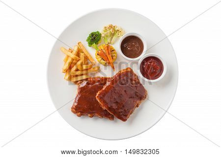 Top view of American style barbecue ribs steak with french fries grilled vegetables pepper sauce and ketchup in ceramic dish isolated on white background