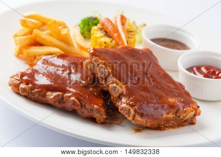 American style barbecue ribs steak with french fries grilled vegetables pepper sauce and ketchup in ceramic dish