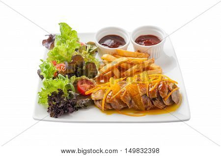 Front view of Modern cuisine style roasted duck breast dressed with orange sauce including french fries vegetables and sauces in ceramic dish isolated on white background