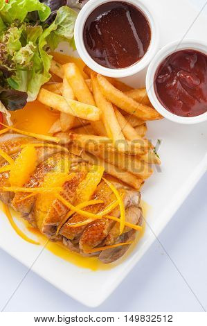 Modern cuisine style roasted duck breast dressed with orange sauce including french fries vegetables and sauces in ceramic dish