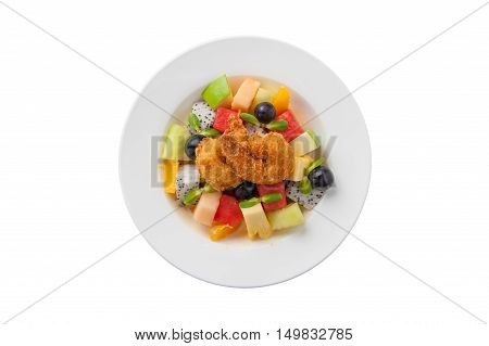 Top view of modern cuisine style fruits salad with deep fried shrimp in ceramic dish isolated on white background