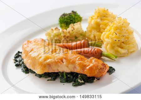 Modern cuisine style fried salmon with spinach mashed potatoes and grilled vegetables in ceramic dish. Clean eating cuisine concept