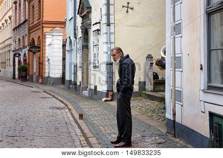 RIGA, LATVIA - OCTOBER 2016: Poor old man at central street of old town in Riga, Latvia
