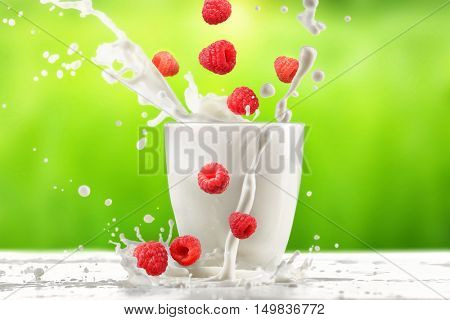 Pouring milk in glass on  table with green background