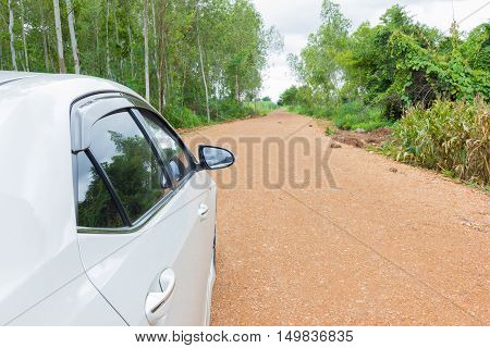 white car stop on the road on the dirt and gravel road.