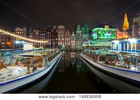 Beautiful typical Dutch dancing houses, Oude Kerk church and tourist boats at the Amsterdam canal Damrak at night, Holland, Netherlands.
