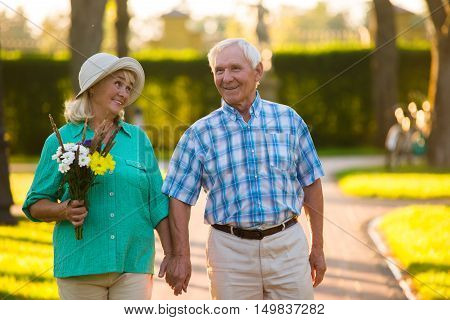 Elderly couple on park background. Senior people are happily smiling. Love of life. Time stops when we're together.