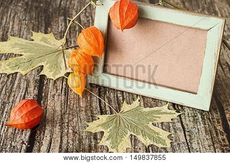 Chinese lantern plants (Physalis ordinary), maple leaves and an old photo frame on a wooden table.