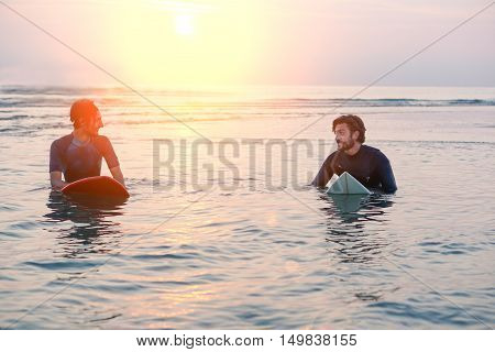 Two men in wetsuits with a surfboard at sunset time inside water - Beach surfers speaking and laughingwaiting for waves at sunrise - Extreme sports and friendship concept - Original sun color tones