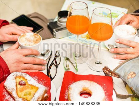 Tourist couple having breakfast in italian bar restaurant - Young people drinking carrot bio juice and capuccino - Food and vacation concept - Warm saturated filter