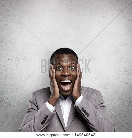 Amazed Young African Businessman Dressed In Formal Wear, Looking Excited And Shocked, Holding Hands
