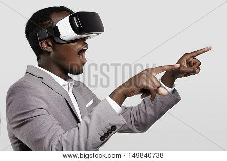 Surprised African Businessman Using Oculus Rift Headset, Experiencing Virtual Reality While Playing