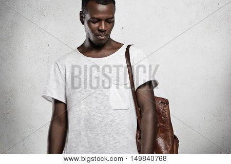 Studio Shot Of Young Handsome African Student Wearing Leather Backpack And White Copy Space T-shirt,