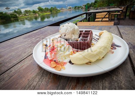 chocolate waffles with vanilla ice cream banana whipped cream and strawberry syrup. chocolate waffles in cozy outdoor cafe.