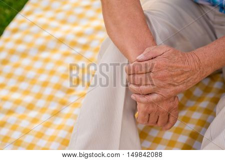 Hands of senior man. Checkered cloth of yellow color. Years pass so fast. Time and loneliness.