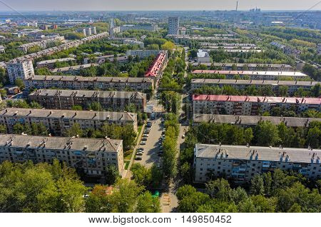 Tyumen, Russia - August 18, 2016: Aerial view on sleeping neighborhood large-panel houses, so called KPD. Geologorazvedchikov street. Power plant on background