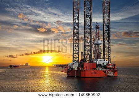 Oil platform and tanker ship on offshore area at sunset.