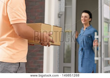 I always use reliable courier. Cropped image of courier holding cardboard box while standing against entrance to apartment