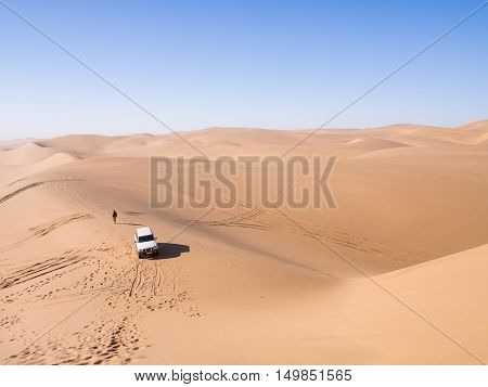 A four by four car on the dunes of the Namib Desert in Sandwich Harbour Namibia. Horizontal orientation wide angle.