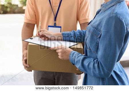 Sign here please. Close up shot of delivery man holding cardboard box while woman putting signature in clipboard