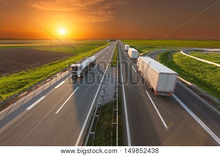 Many white trucks towards the sun. Transportation scene on the highway at beautiful sunset. Freight fast delivery on the motorway near Belgrade Serbia.