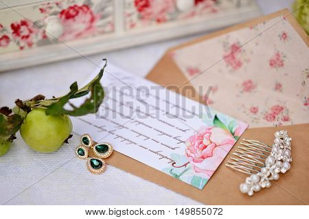 An envelope with a wedding invitation in conjunction with the bride's jewelry.