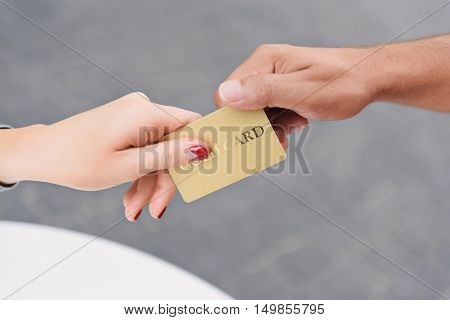 Payments have never been easier. Cropped shot of woman paying at cafe and handing over her credit card to waiter while staying outdoor