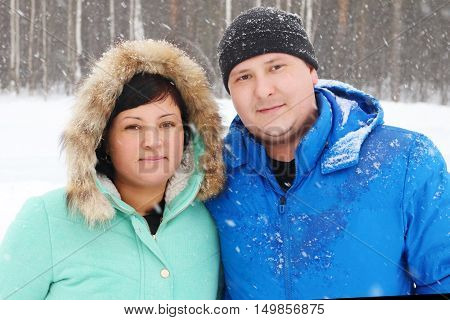 Happy fat couple looks at camera in park during snowfall in winter day