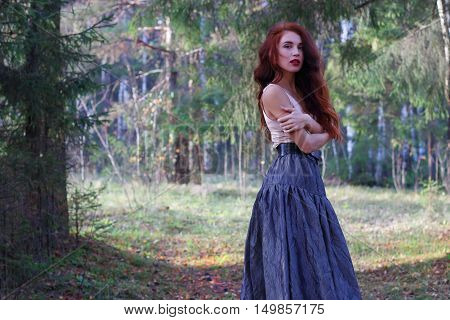 Sexy woman in skirt and belt poses on wind in sunny autumn forest