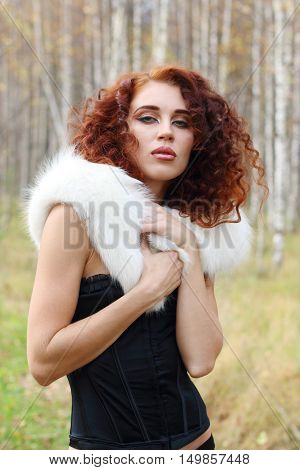 Beautiful woman in corset with white fur poses in autumn forest