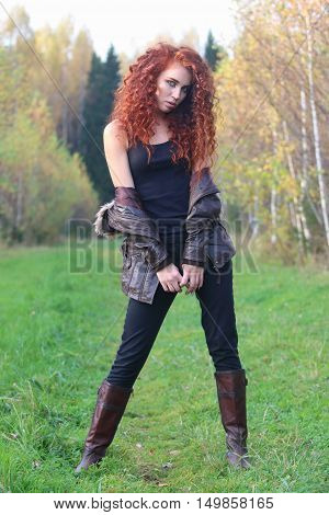 Pretty girl with red curly hair stands among trees on green grass