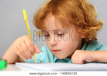 childhood and learning concept, close up of a cute redhead boy drawing on paper in kindergarten