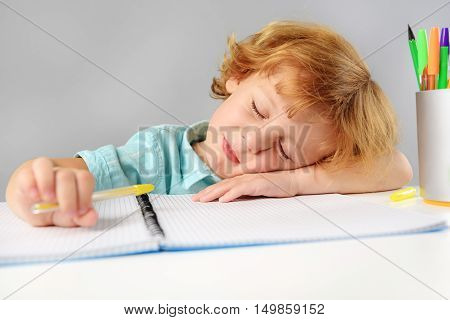 childhood and learning concept, boy sleeping at desk
