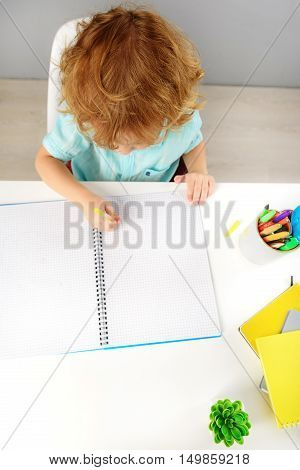 childhood and learning concept, top view of intelligent redhead kid sitting and drawing on paper with pen in elementary school