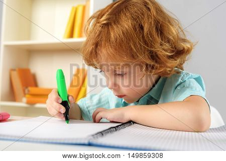 childhood and learning concept, intelligent little artist drawing on paper with highlighter