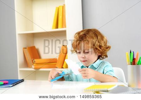 childhood and learning concept, child learning how to use scissors